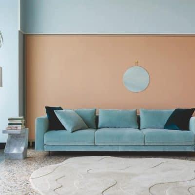 Enki sofa in pale green velvet, Asola floor light and Pierre Paulin's Gavrinis 3 rug design against soft terracotta wall