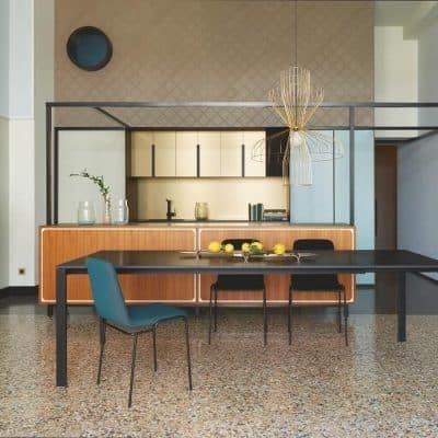 Allungami extending dining table in anthracite Fenix. Kermes open storage unit with gold interior. CM131 original Pierre Paulin design